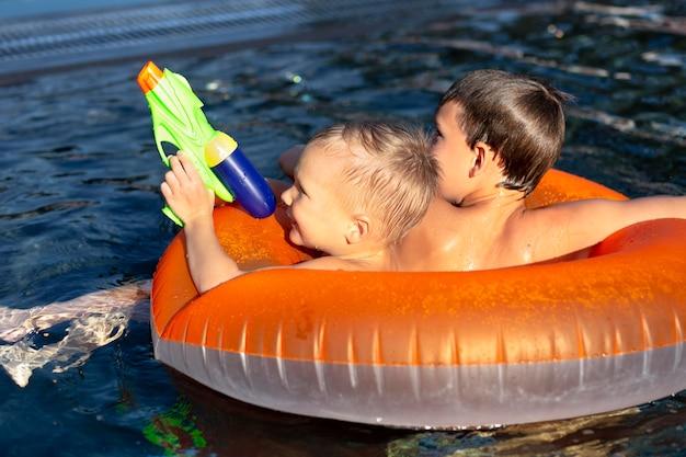 Jungs haben spaß im schwimmbad mit schwimmer und wasserpistole