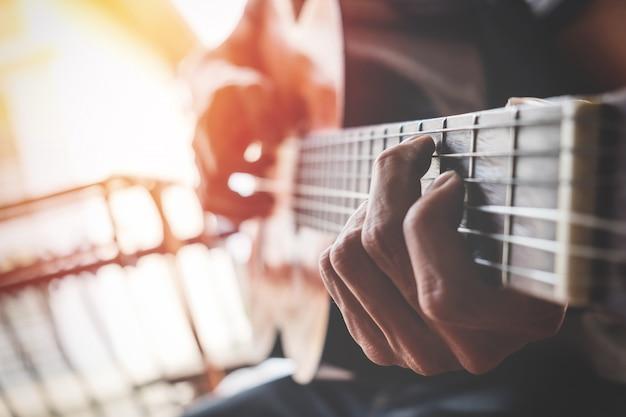 Jungs hand mit einer gitarre