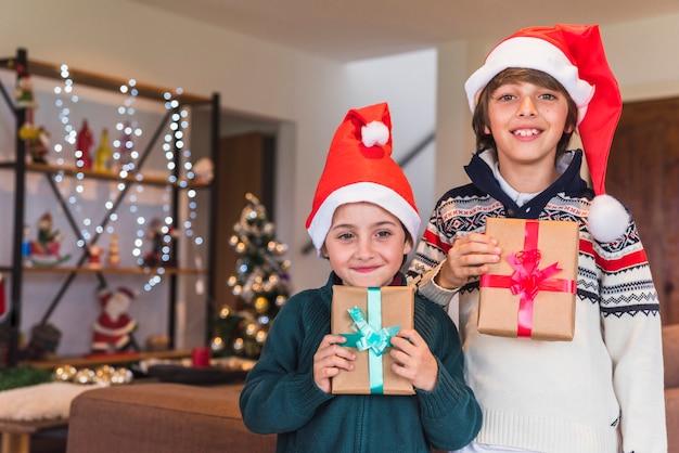 Jungs in santa hüte mit geschenkboxen