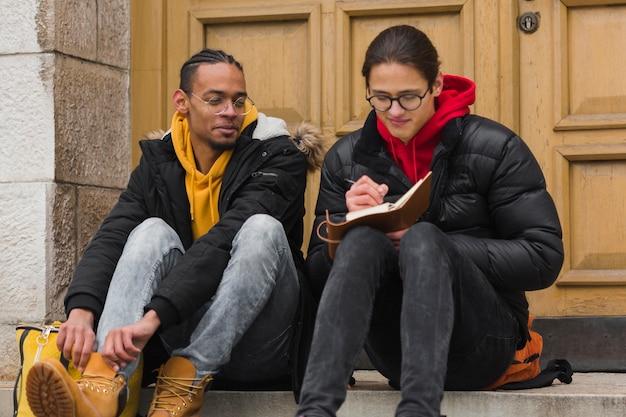 Jungs sitzen auf treppen mit notizbuch