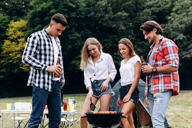 Jungs stehen neben einem grill. kochende mädchen und männer, die ein bier und ein lächeln halten