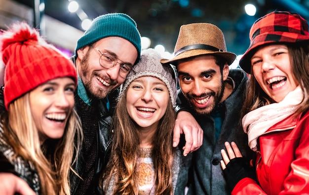 Jungs und mädchen, die besten freunde, die nachts ein selfie auf warmer modekleidung machen