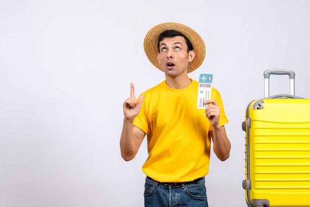 Jungtourist der vorderansicht im gelben t-shirt, das nahe gelbem koffer hält, der ticket an der decke zeigt