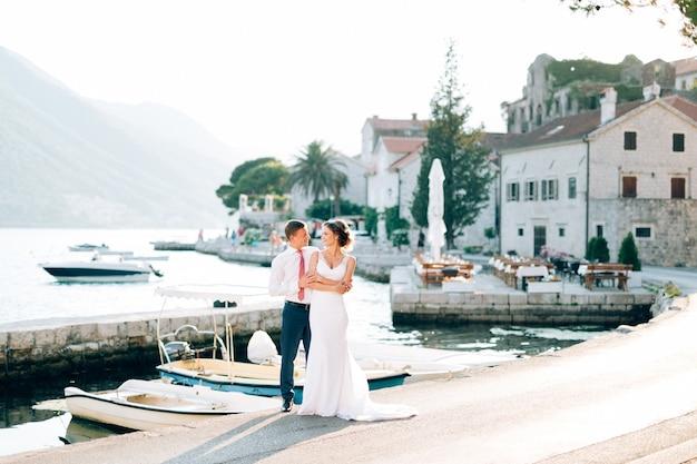 Jungvermählte umarmen sich auf dem pier in der nähe der boote vor dem hintergrund der alten