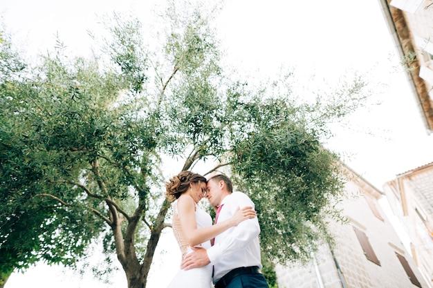 Jungvermählte umarmen sich vor dem hintergrund eines alten weißen backsteinhauses und einer grünen baumansicht von unten