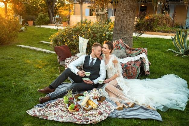 Jungvermählten-abendessen auf dem rasen bei sonnenuntergang. ein paar sitzt und trinkt tee bei sonnenuntergang in frankreich
