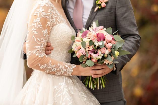 Jungvermählten am hochzeitstag, hochzeitspaar mit hochzeitsstrauß von blumen, braut und bräutigam