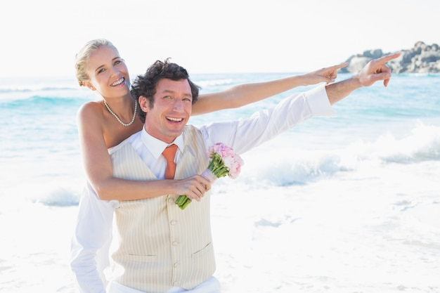 Jungvermählten, die auf etwas lächelt an der kamera zeigen