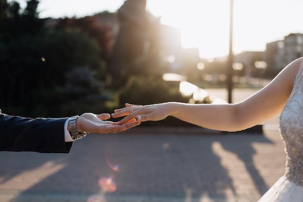 Jungvermählten, die liebevoll sind, berühren sich ihre hände