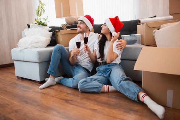 Jungvermählten feiern weihnachten oder neujahr in ihrer neuen wohnung. junger glücklicher mann und frau trinken wein, feiern umzug in ein neues zuhause und sitzen zwischen kisten.