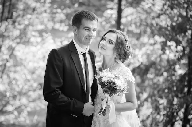 Jungvermählten. glückliches hochzeitspaar. braut und bräutigam lächeln und umarmen sich im park