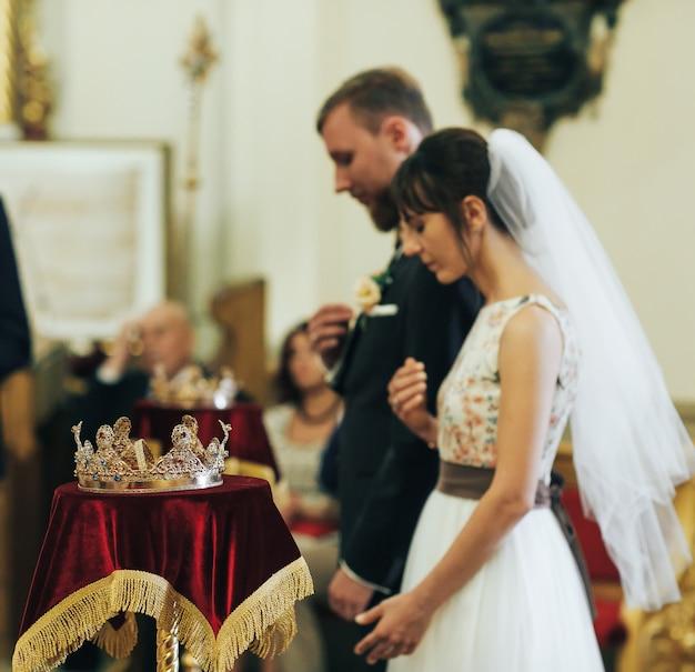 Jungvermählten in der kirche. priester feiern hochzeitsmesse in der kirche