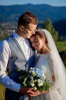 Jungvermählten lächeln und umarmen sich auf der wiese oben auf dem berg. hochzeitsspaziergang im wald in den bergen, die sanften gefühle des paares