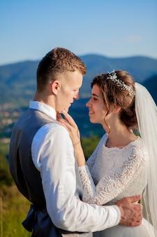 Jungvermählten lächeln und umarmen sich auf der wiese oben auf dem berg. hochzeitsspaziergang im wald in den bergen