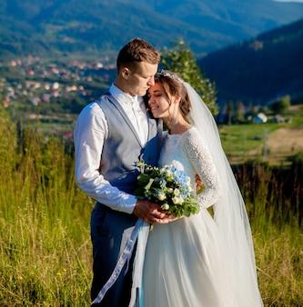 Jungvermählten lächeln und umarmen sich auf der wiese oben auf dem berg