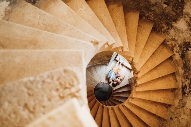 Jungvermählten liegen händchen haltend auf der wendeltreppe der alten burg von oben