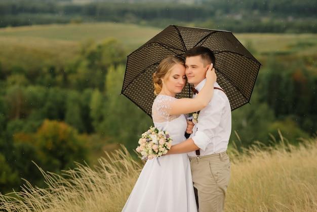Jungvermählten stehen mit einem regenschirm vor einer wunderschönen landschaft.