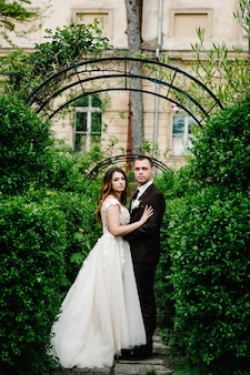 Jungvermählten stehen und schauen in die kamera auf dem hintergrundbogen mit viel grün im garten. hochzeitszeremonie über die natur im park.