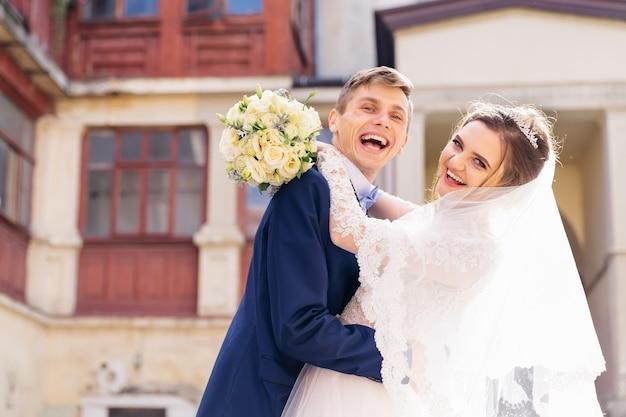 Jungvermählten umarmen sich und schauen in die kamera