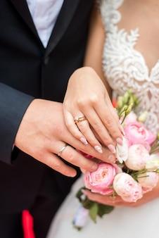 Jungvermähltenhände mit ringen. hochzeitsstrauß auf dem hintergrund der hände der braut und des bräutigams mit einem goldenen ring