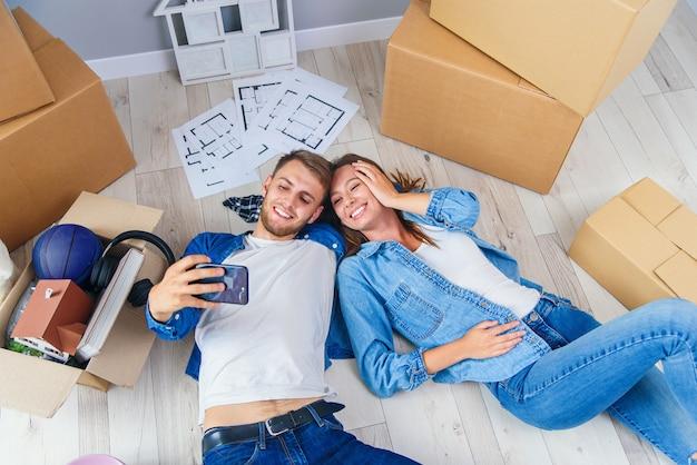 Jungvermähltenpaar liegt auf dem holzboden ihrer neuen wohnung und macht selfie per smartphone. draufsicht.