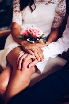 Jungvermähltenpaar mit ihren eheringen und rosenstrauß, die an ihrem hochzeitstag streicheln. braut und bräutigam zeigen ihre hand mit den ringen.