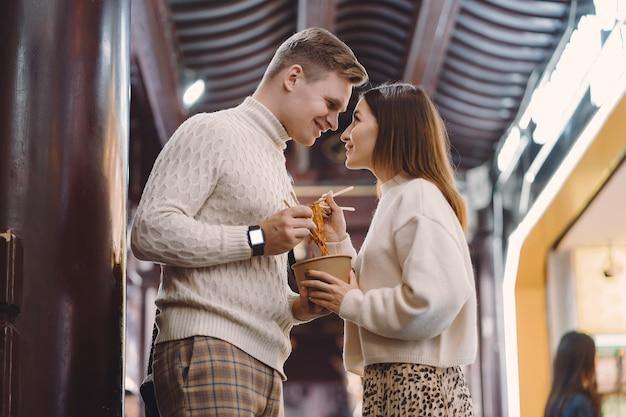 Jungvermähltenpaare, die nudeln mit essstäbchen in shanghai außerhalb eines lebensmittelmarktes essen
