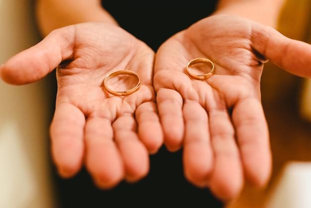Jungvermähltenringe in den händen der braut und des bräutigams.