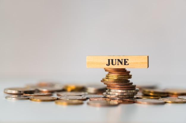 Juni-holzklotz auf stapel von münzen