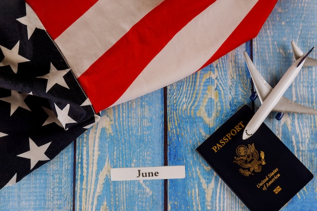 Juni monat des kalenderjahres, reisetourismus, auswanderung der amerikanischen flagge der usa mit us-pass und passagiermodell flugzeug