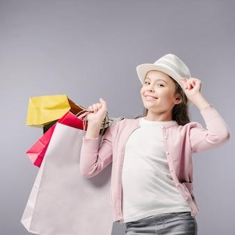 Junior, der mit Einkaufstaschen und Hut aufwirft