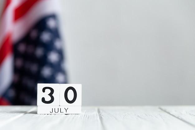 Junitag auf holzklötzen mit der us-flagge im rücken