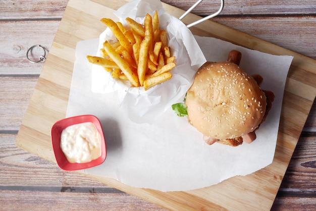 Junk-food auf einem schneidebrett auf holztisch-draufsicht