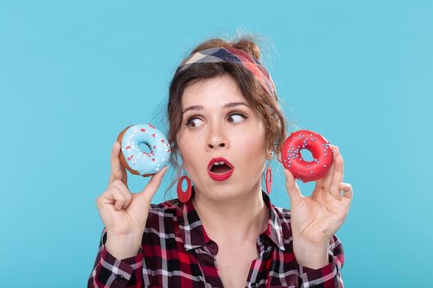 Junk food, diät und ungesundes lifestyle-konzept - pin-up-frau mit donuts über dem blau
