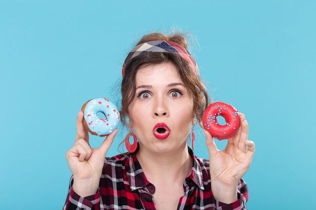 Junk food, diät und ungesundes lifestyle-konzept - pin-up-frau mit donuts über der blauen oberfläche.