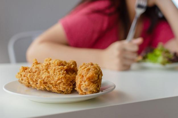 Junk-food-konzept. gebratenes huhn auf schreibtisch mit der jungen hübschen frau, die zu hause frischgemüsesalat für gute gesundheit isst