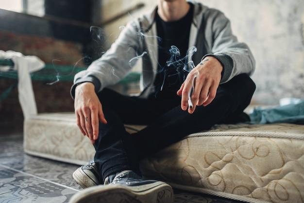 Junkie sitzt auf der matratze und raucht zigarette