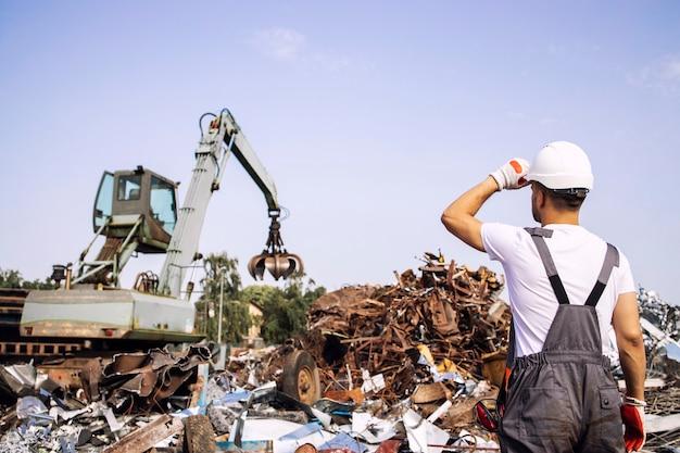 Junkyard worker supervisor, der industriekranmaschinen betrachtet, die metallteile zum recycling anheben