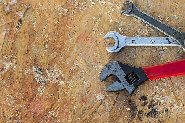 Justierbarer schlüssel, schlüsselwerkzeuge auf holztischhintergrund