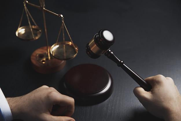 Justiz- und rechtskonzept. männlicher anwalt im büro mit messingskala auf holztisch, reflektierte ansicht