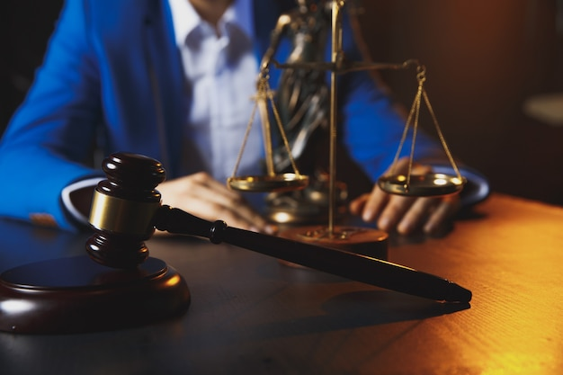 Justiz- und rechtskonzept. männlicher anwalt im büro mit messingskala auf holztisch, reflektiertref