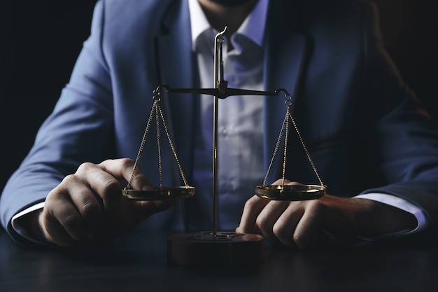 Justiz- und rechtskonzept männlicher anwalt im büro mit messingwaage auf hölzernem tablereflekt