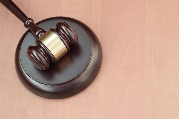 Justizschläger auf holzschreibtisch in einem gerichtssaal während eines gerichtsverfahrens. gesetzeskonzept und leerer raum für text. richter hammer
