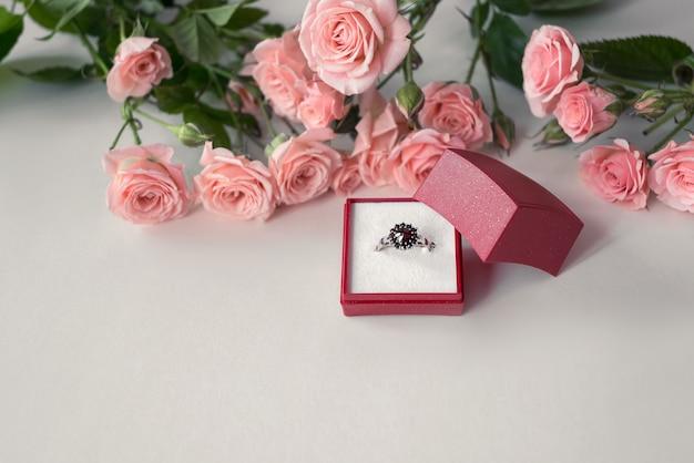 Juwelenbesetzter verlobungsring in geöffneter roter schmuckschatulle, umgeben von blassrosa rosen. valentinstag feiern