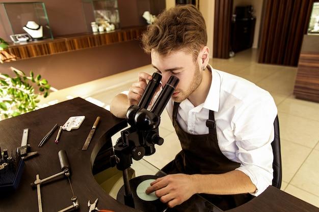 Juwelier untersucht den ring durch ein mikroskop