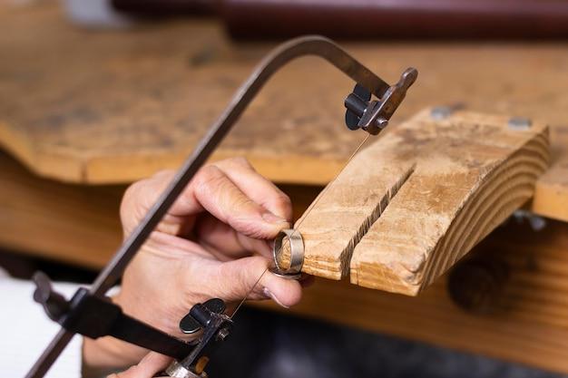 Juwelierhände arbeiten an einem ring