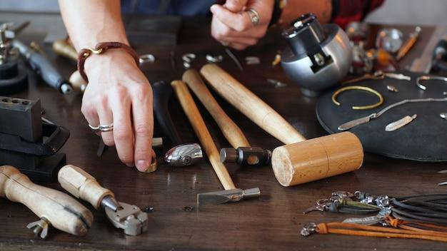 Juweliermeister macht schmuck am arbeitsplatz. arbeit eines juweliers nahaufnahme