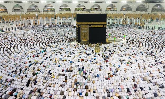 Kaaba in makkah mit einer menge muslimischer menschen auf der ganzen welt, die zusammen beten