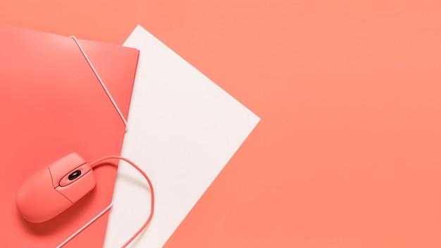 Kabelgebundenes mauspapier und orangefarbener ordner mit elastischem verschluss
