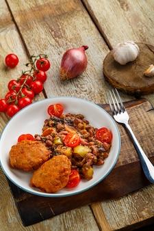 Kabeljau-koteletts mit kartoffeln und gemüse in der nähe zutaten.